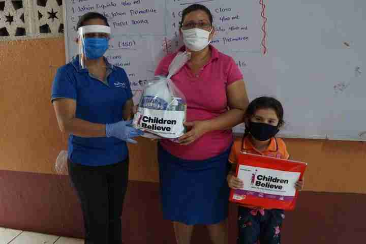 Worker hands mom emergency hygiene kit, while child holds education kit