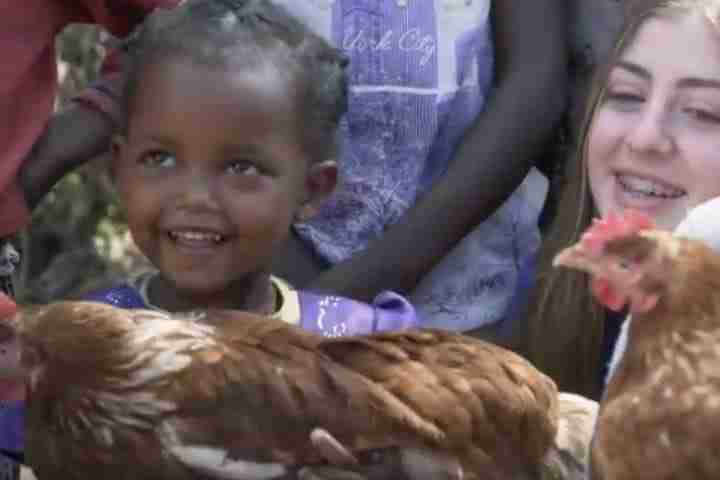 Teen and children pose with chickens