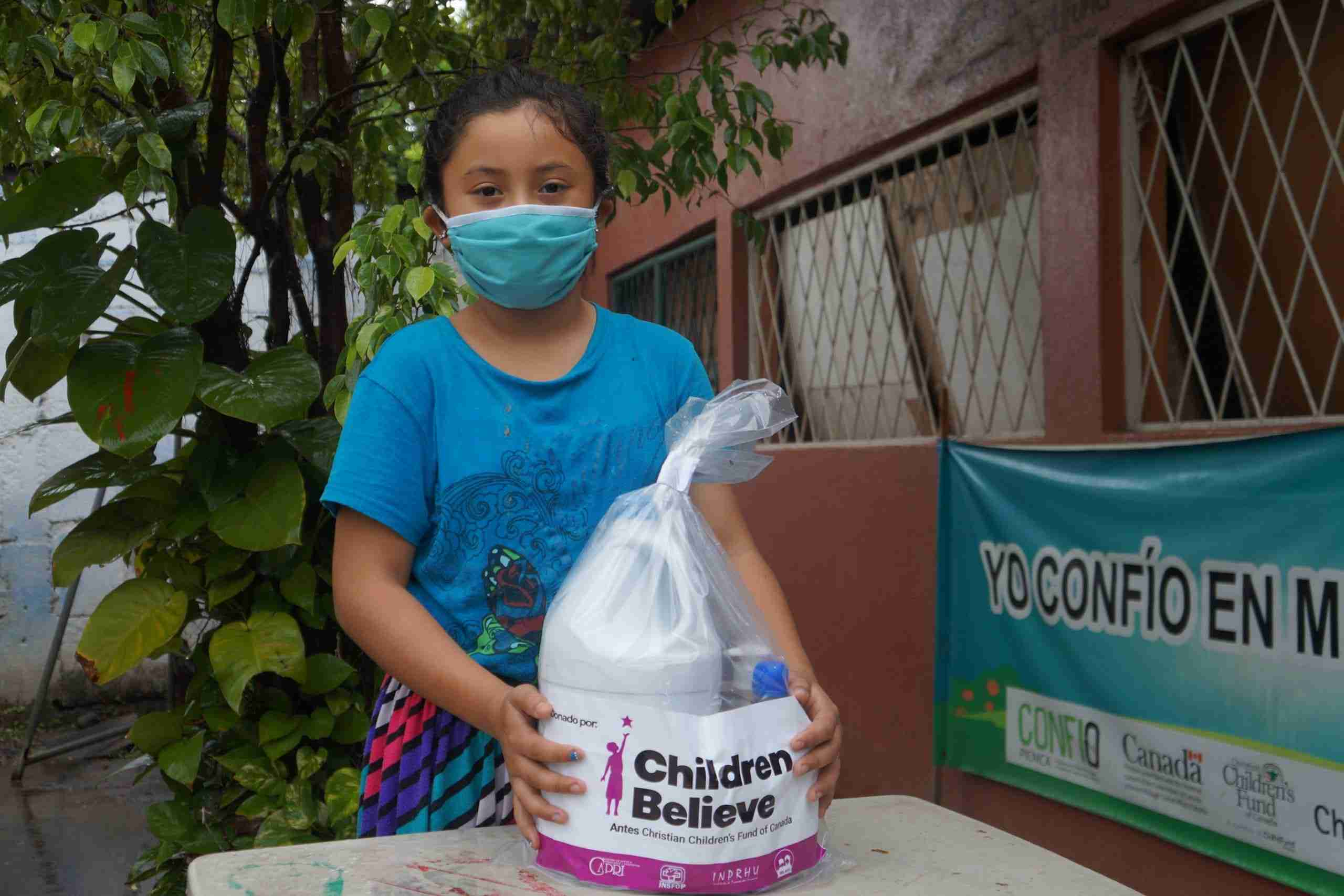 Girl with mask holds hygiene kit