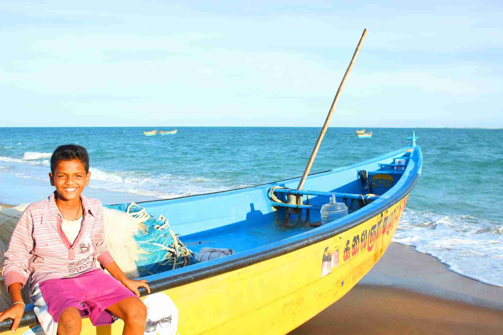 Boy sits on fishing boat near ocean