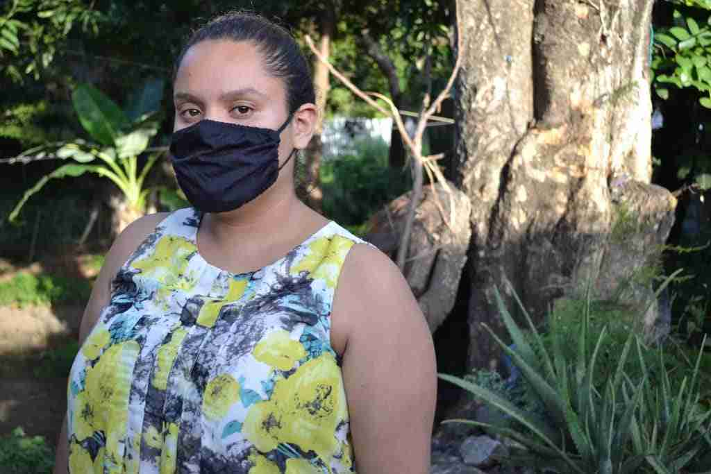 Young mother stands outside with mask on