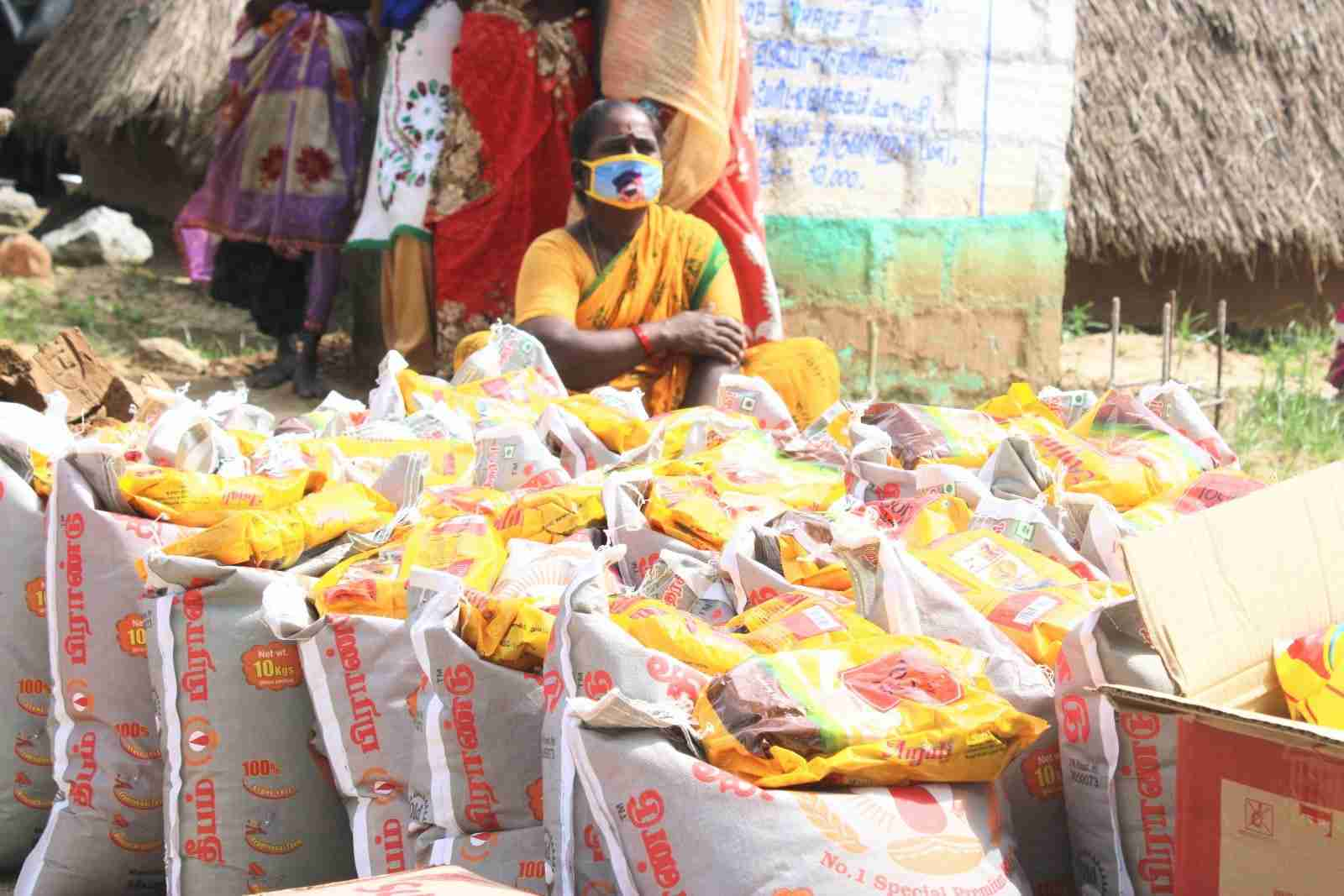 Woman sits among bags of rice