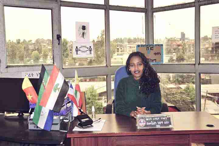 Women sits at her desk overlooking Addis Ababa, Ethiopia