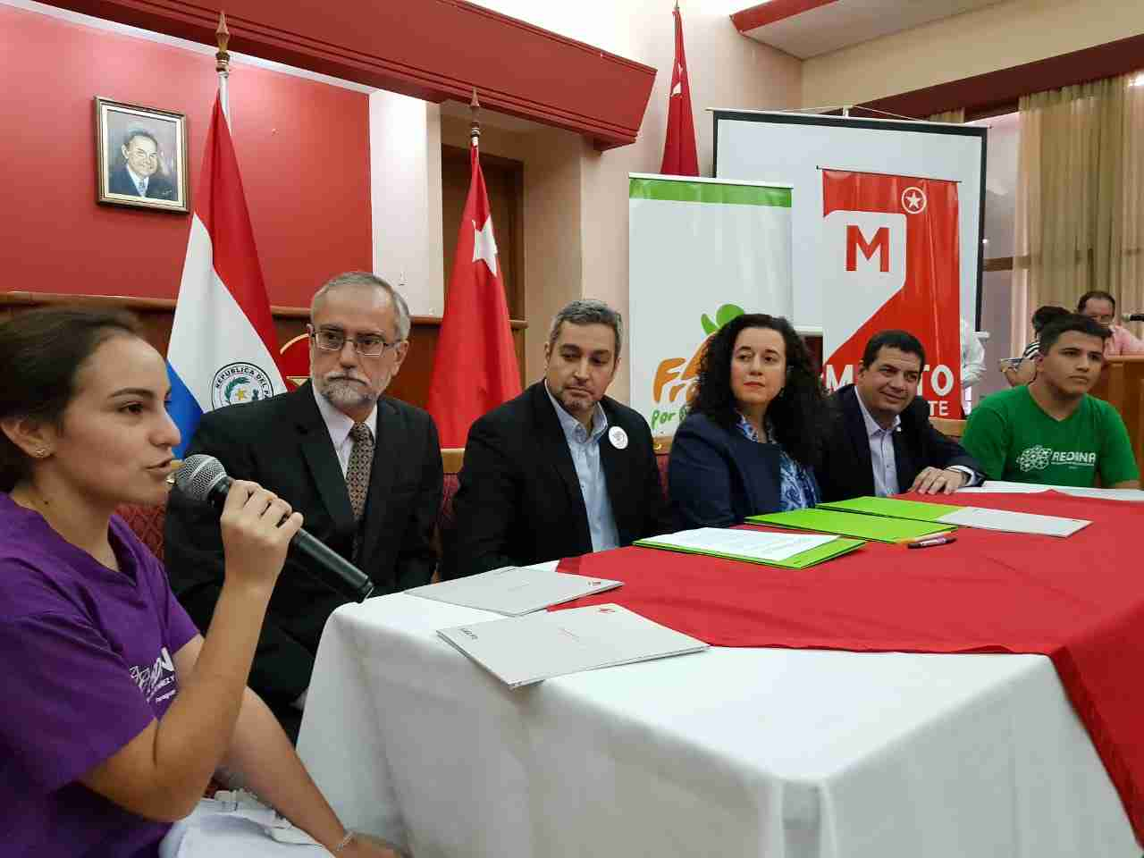 Youth speaks at table filled with dignitaries