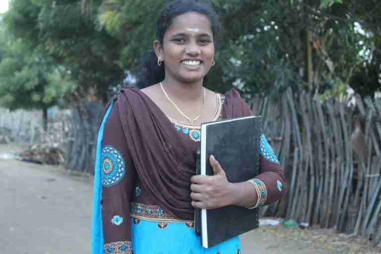 Anitha smiles while holding her notebook