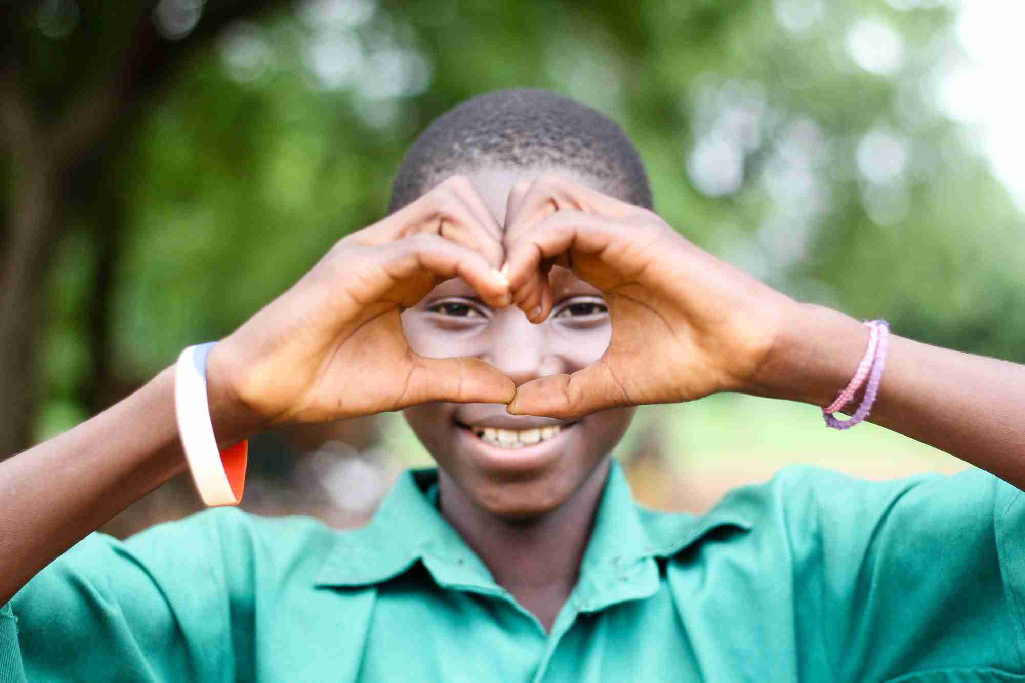 Boy forms a heart with his hands