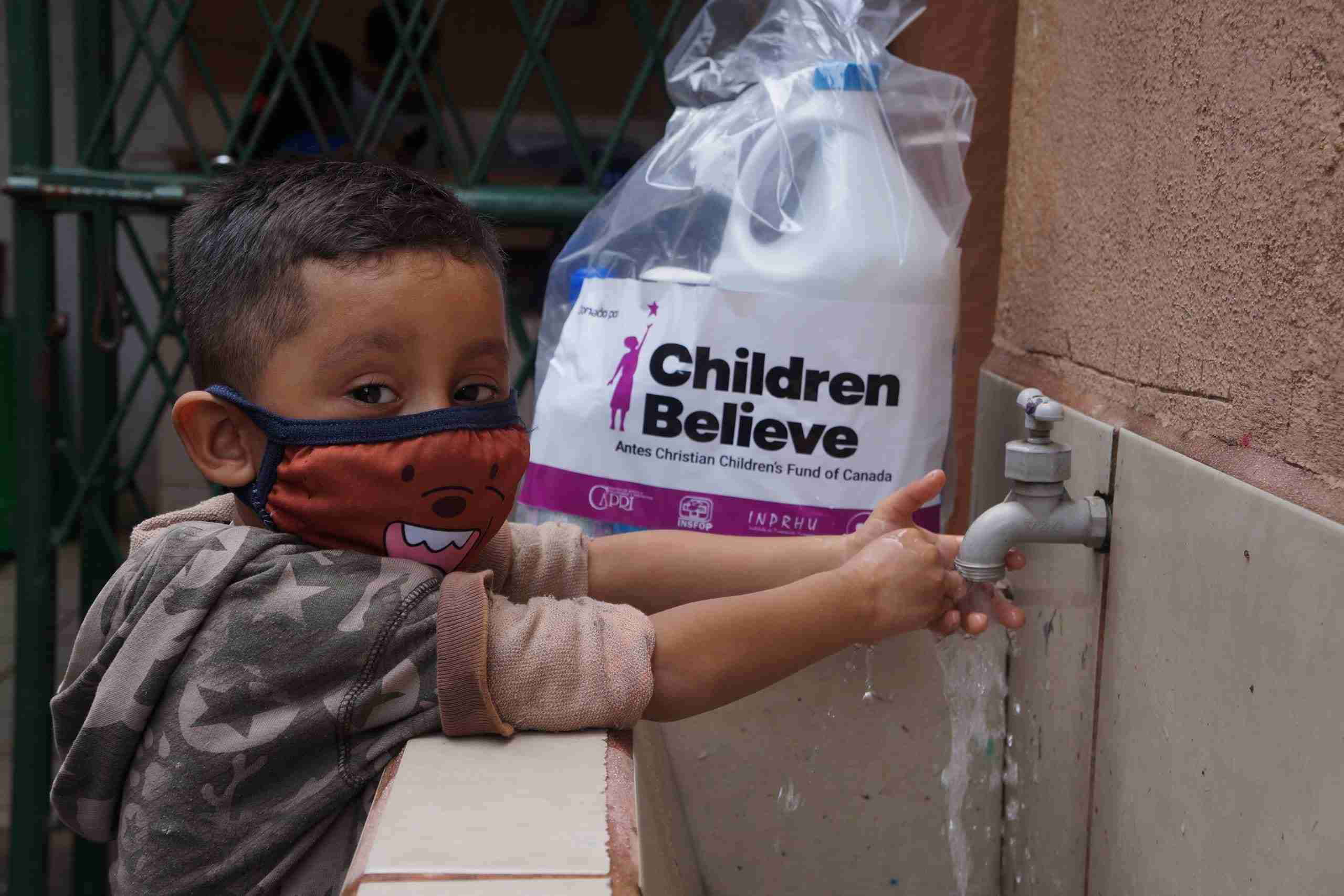 Boy with mask washes his hands