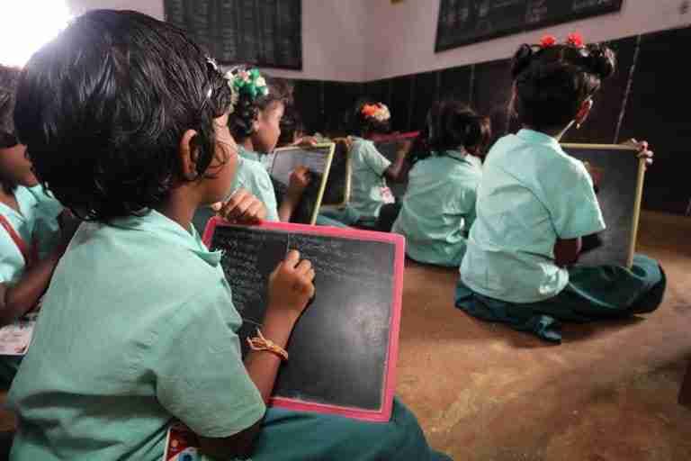 Kids sit on floor in classroom with mini chalkboards