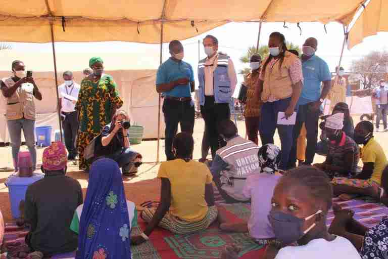Adults and children gather under a tent