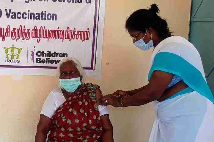 Woman gives another woman a vaccine