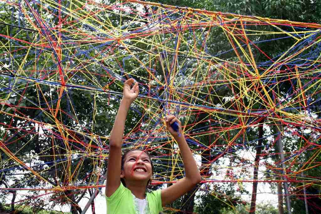 Child threads yarn between trees