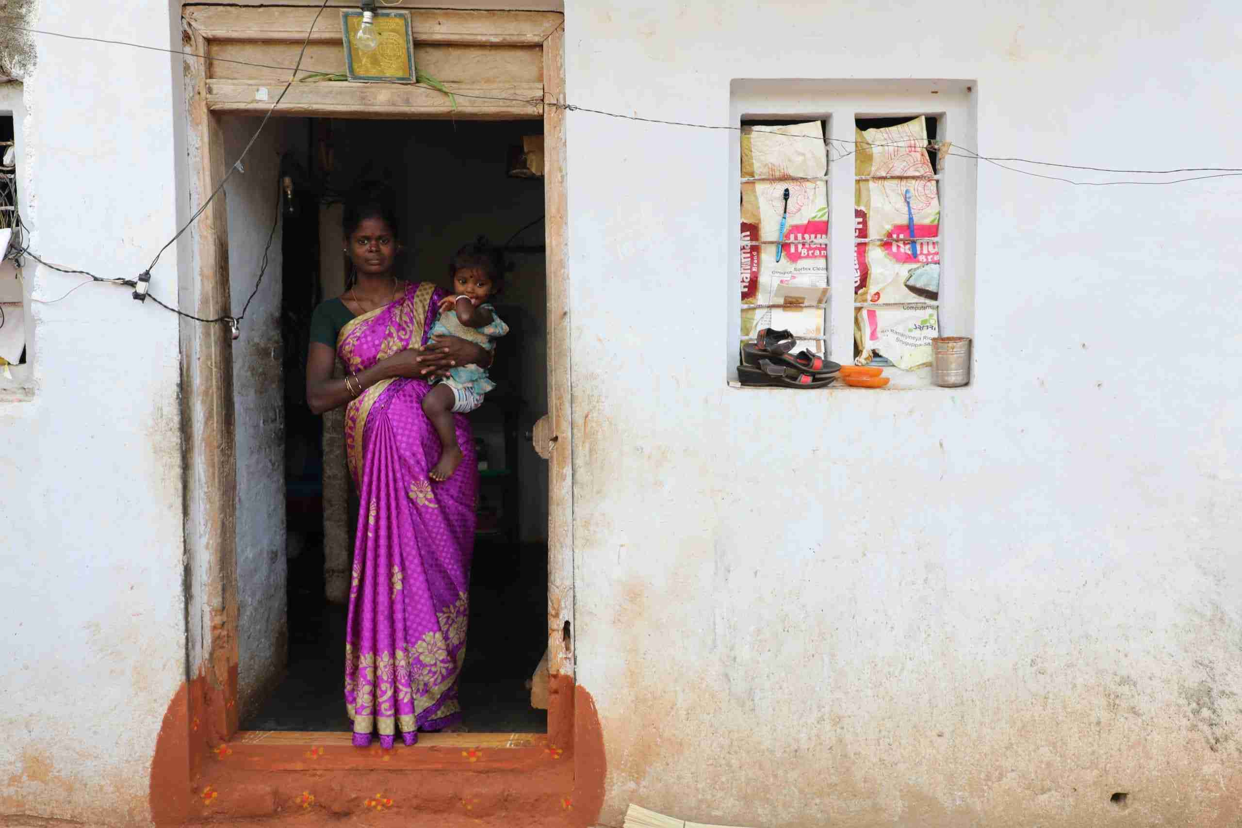 Woman holds a baby in doorway