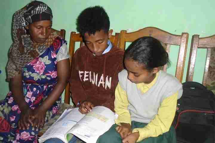 Children and mother look at schoolwork