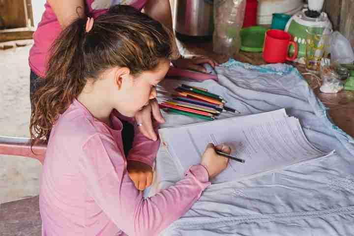 Girl works on schoolwork at desk