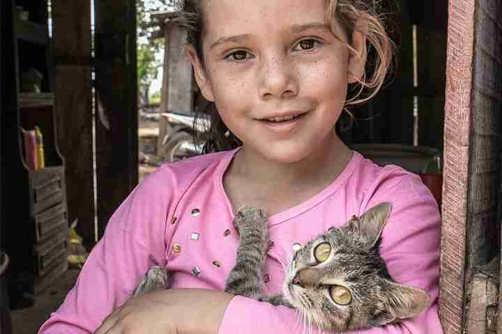 Girl smiles while holding cat