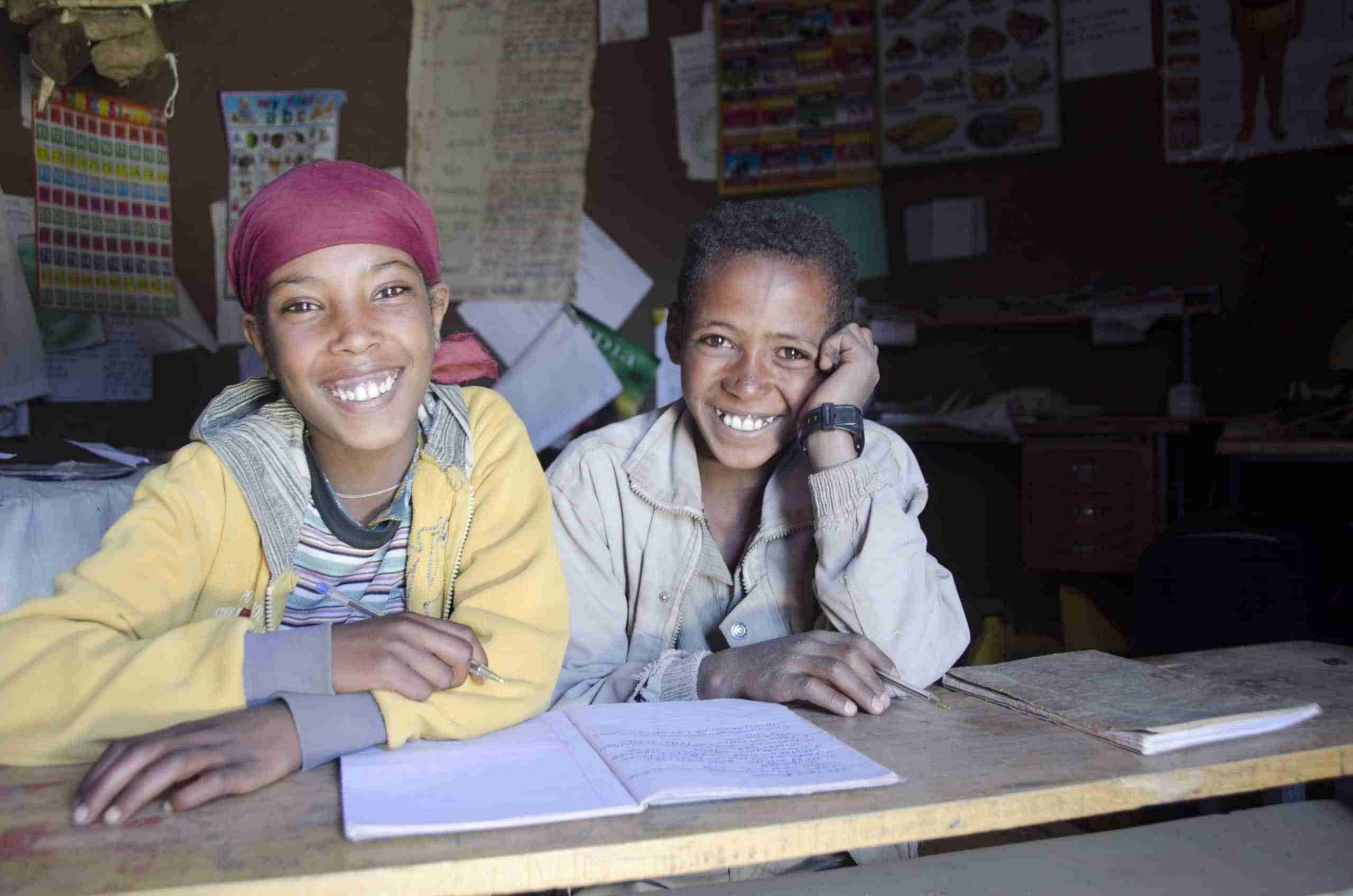 A girl and boy sit side by side with a notebook open on their desk in a classroom