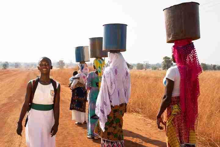 Schoolgirl walks past women walking with water on their heads