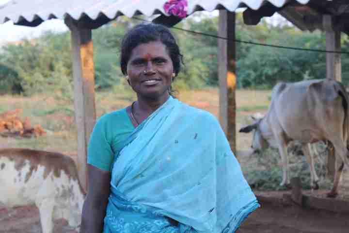 Women in blue sari smiles outside farmhouse with tin roof.
